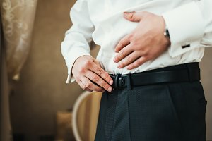 Groom prepear for ceremony, fasten his belt