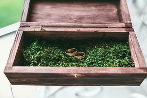Beautiful golden wedding rings inside a vintage wooden box