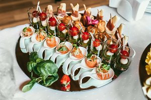 Delicious sushi rolls on black plate, decorated fruit snacks