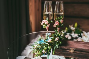 Two champagne glasses decorated with small boutonniere