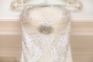 A close up of a wedding dress with a large silk bow
