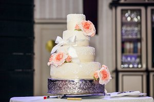 Wedding cake decorated with roses, lace and bow