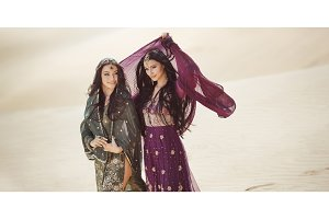Travel concept. Two gordeous women sisters traveling in desert. Arabian Indian movie stars.