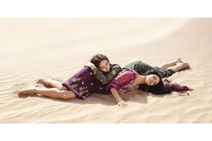 Women thirsty laying in a desert. Lost in desert durind sandshtorm