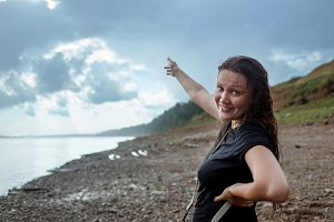The girl in wet clothes under a heavy rain outdoors. Woman point to rain clouds