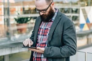 Bearded stylish man with tablet in hands