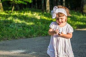 little girl draws on asphalt