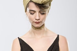 Sophisticated blonde woman with golden turban on white background