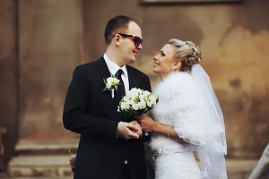 Groom in sunglasses smiles to bride