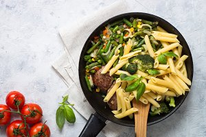 Pasta penne with green vegetables and meat cutlets.