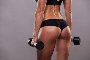 Athletic booty of girl with dumbbells isolated on grey background with copyspace