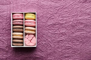 Box of colorful macarons on textured background