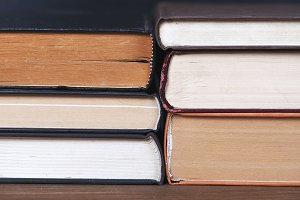 Close-up of books stacked on brown wooden table and black background.