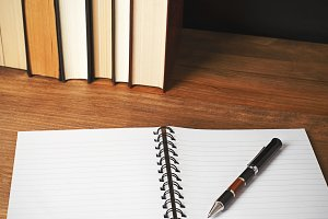 Opened notepad with a pen on top next to several books on wooden table.