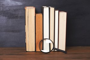 Magnifying glass over several books lying on a wooden table.