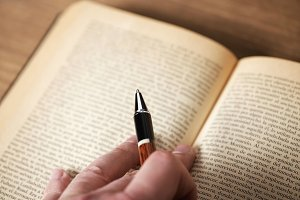 Hand with a pen on a book. Horizontal shoot.