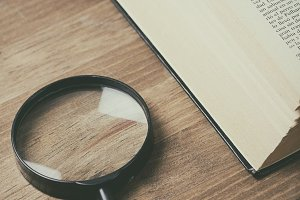 Magnifying glass on wooden table next to an open book. Vertical shoot.