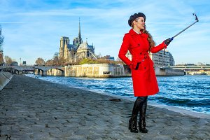 smiling tourist woman in Paris taking selfie using selfie stick