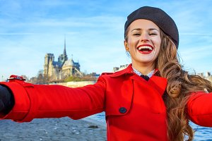 smiling woman on embankment in Paris, France taking selfie