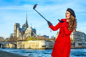 happy traveller woman in Paris taking selfie using selfie stick