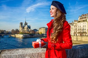 woman in Paris with Christmas present box looking into distance