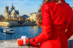 Seen from behind woman in Paris with Christmas present box