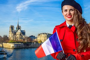 traveller woman in Paris with French flag looking into distance