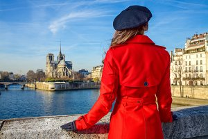 woman on embankment near Notre Dame de Paris in Paris, France