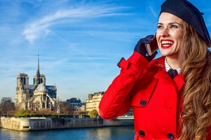 smiling modern tourist woman in Paris, talking on smartphone