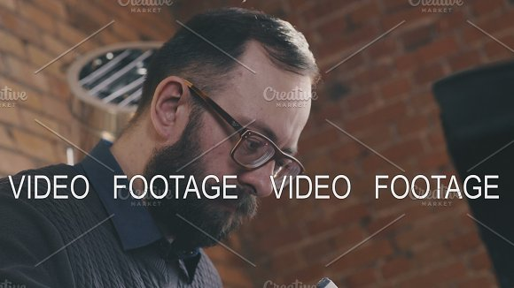Stylish Man With A Beard And Glasses Works In A Loft-style Office