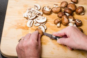 Cook cutting up mushrooms