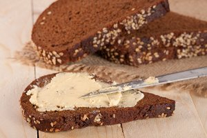 slices of black bread with sesame seeds and butter on a light wooden background