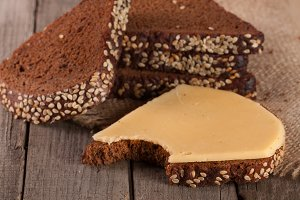 slices of black bread with sesame seeds and cheese on the old wooden background