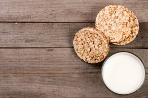 glass of milk with grain crispbreads on old wooden background with copy space for your text. Top view