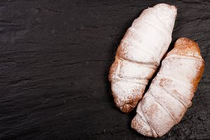 two croissants sprinkled with powdered sugar on black stone background with copy space for your text. Top view