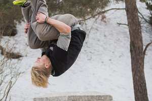 Teenager blonde hair man training parkour jump in the snow covered park