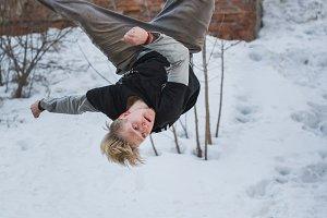 Backflip parkour in winter snow park - blonde hair teenager