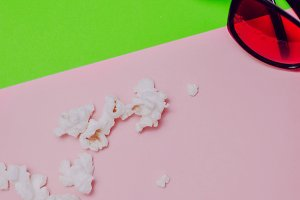 Popcorn and 3D glasses on green and pink background.