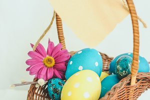 Happy Easter concept. Wicker basket full of colorful painted eggs and note paper hanging on white background