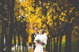 Groom looks at a bride in the park