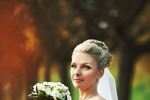Bride looks proud in the park