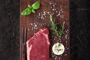 Raw steak with herbs and salt