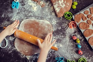 Young girl's hands sheeting dough with rolling pin