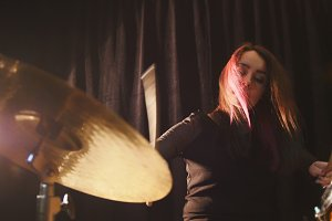 Flowing black hair - beauty girl plays drum rock at garage