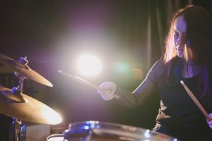 Young woman percussion drummer performing with drums