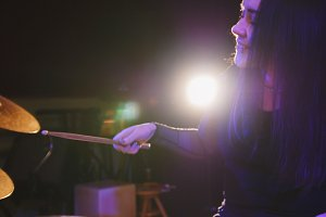 Girl rock musician - female drummer performing