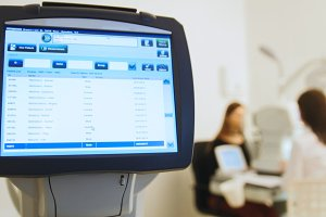 Ophthalmologist in eyes clinic doing diagnostic with vision of patient by modern computer systems - high technology health care