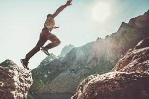 Man jumping to the sun in mountains