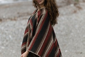 Portrait of happy brunette woman on the beach wearing poncho