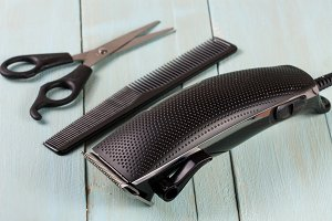 hair trimmer with comb and scissors on the wooden background